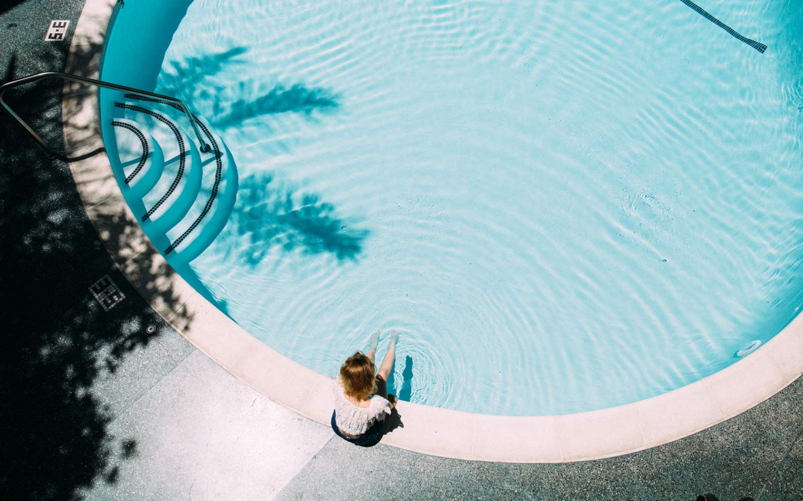 child sitting at the poolside