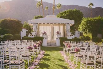 Outdoor wedding area with gazebo, chairs, and aisle with flower petals