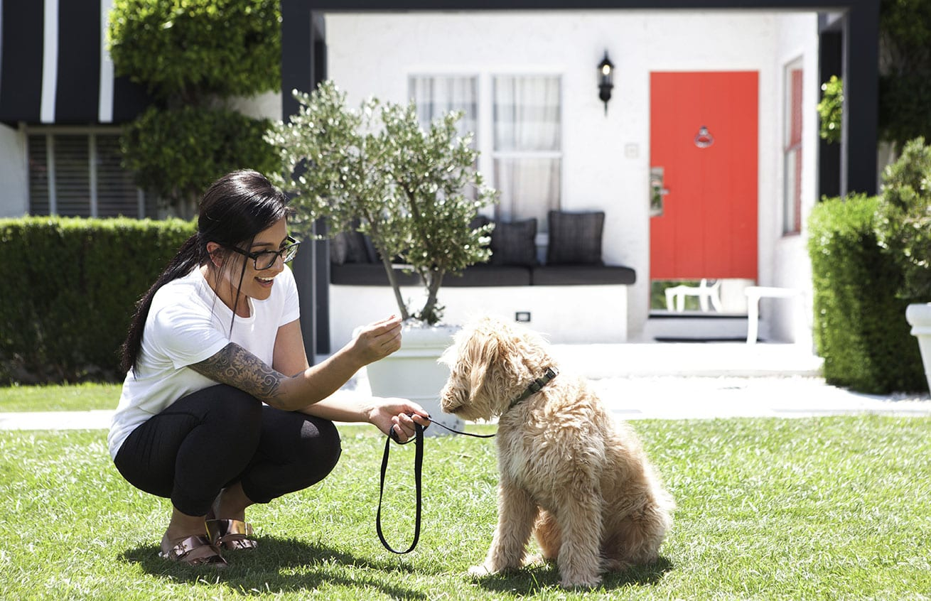 Woman crouching outdoors, smiling, holding a dog attached to a leash