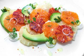 Plate of sliced citrus fruit and avocados