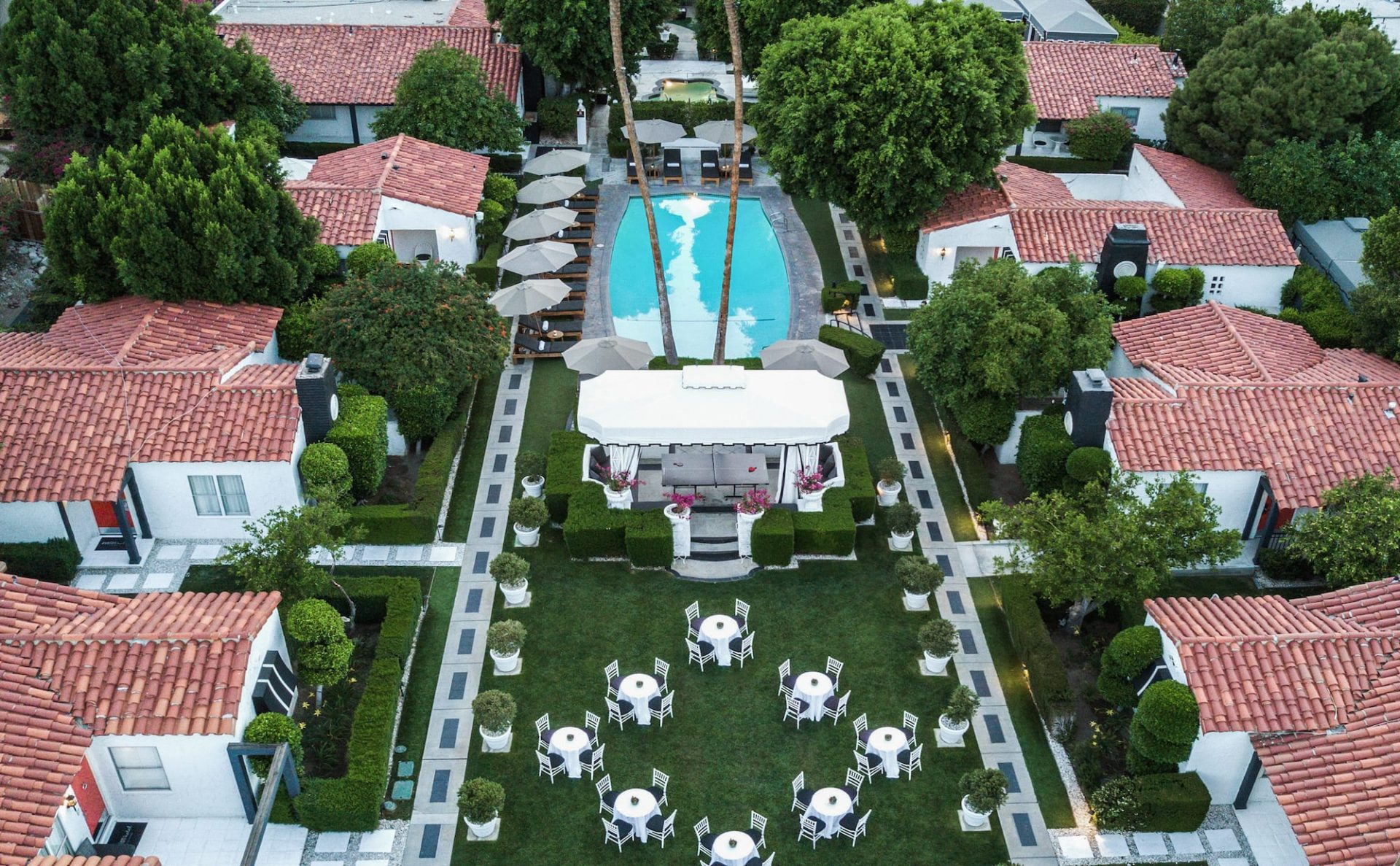 overhead view of large outdoor lawn with chairs and tables, surrounded by smaller buildings