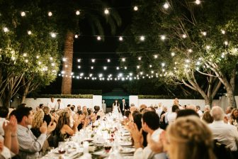 Reception dinner where various people are seated at tables outdoors, under string lights