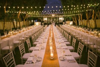 Large table set up for reception dinner outdoors at nightime
