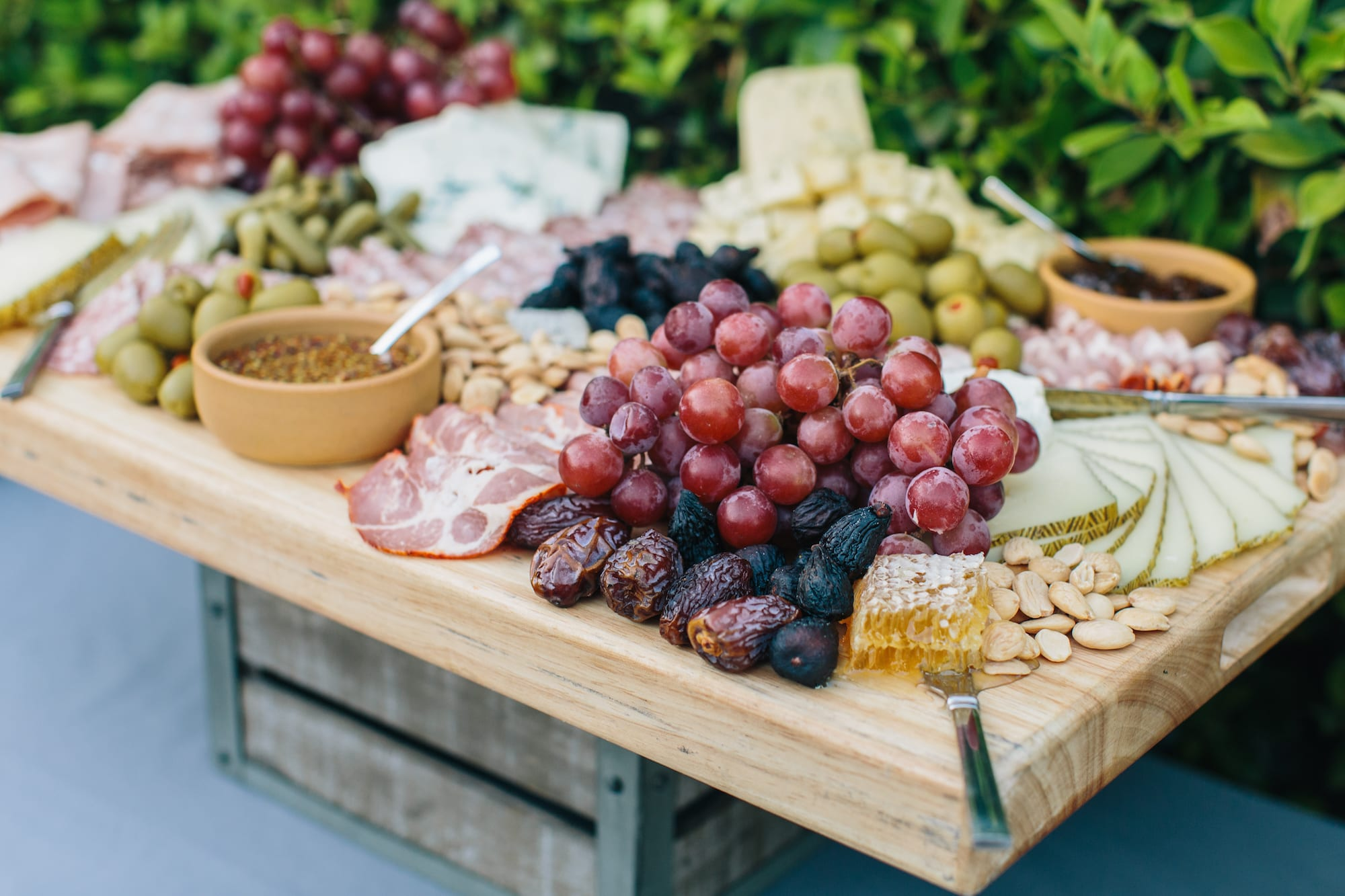 Closeup of wooden table with grapes, dates, nuts, olives and cheeses