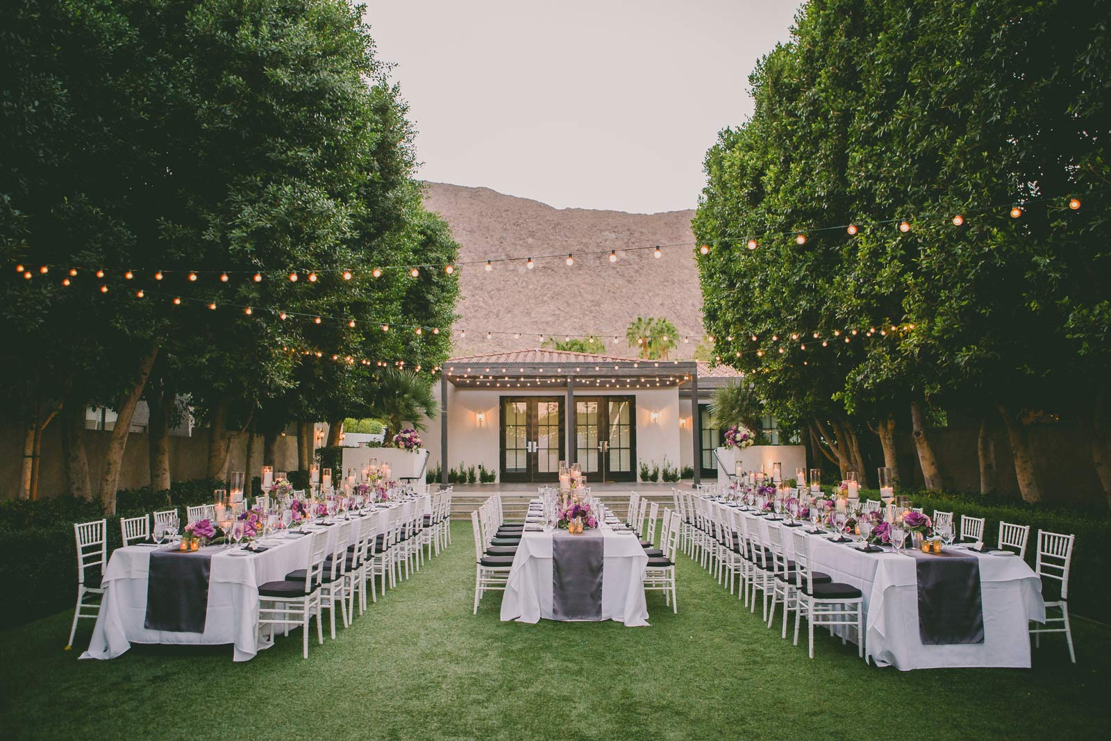 Lawn surrounded by trees and tables and chairs elegantly set