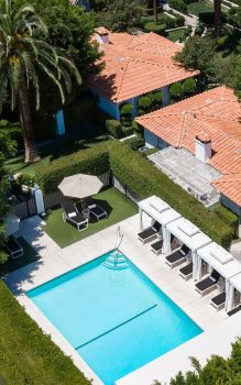 Overhead view of small, square pool, surrounded by hedges, trees, and buildings with Spanish tile roofs