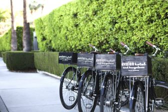 Closeup of bicycles parked outdoors, with small wooden boxes attached in the rear, bearing the Avalon Hotel logo