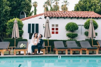 Wedding couple sitting on a lounge chair next to a pool