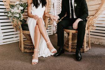 Closeup from the neck down of couple elegantly dressed, sitting down and holding hands
