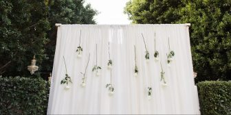 outdoor curtain with white roses hanging from it